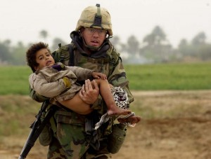 Pfc. Joe Dwyer carried a young Iraqi boy who was injured during a heavy battle between the U.S. Army's 7th Cavalry Regiment and Iraqi forces near the village of Al Faysaliyah, Iraq, on March 25, 2003. Dwyer died of an apparent overdose at his home in North Carolina on June 29, 2008. Photo credit: Warren Zinn / Military Times file